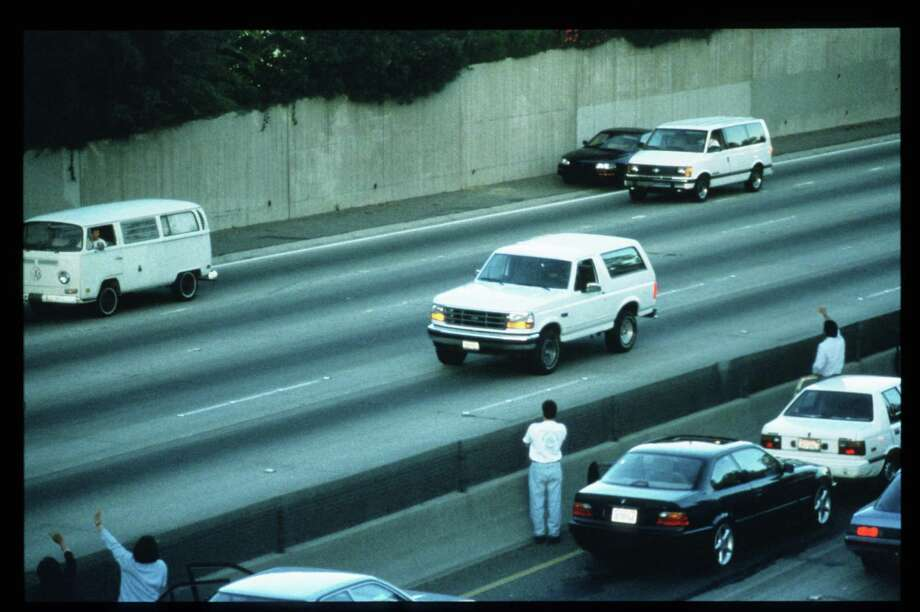 Motorists wave as police cars pursue the Ford Bronco driven by Al Cowlings, carrying fugitive murder suspect O.J. Simpson, on a 90-minute slow-speed car chase June 17, 1994, on the 405 freeway in Los Angeles. Four days earlier, Simpson's ex-wife Nicole Brown Simpson and Ronald Goldman were found murdered. Photo: Jean-Marc Giboux, Getty Images / Hulton Archive
