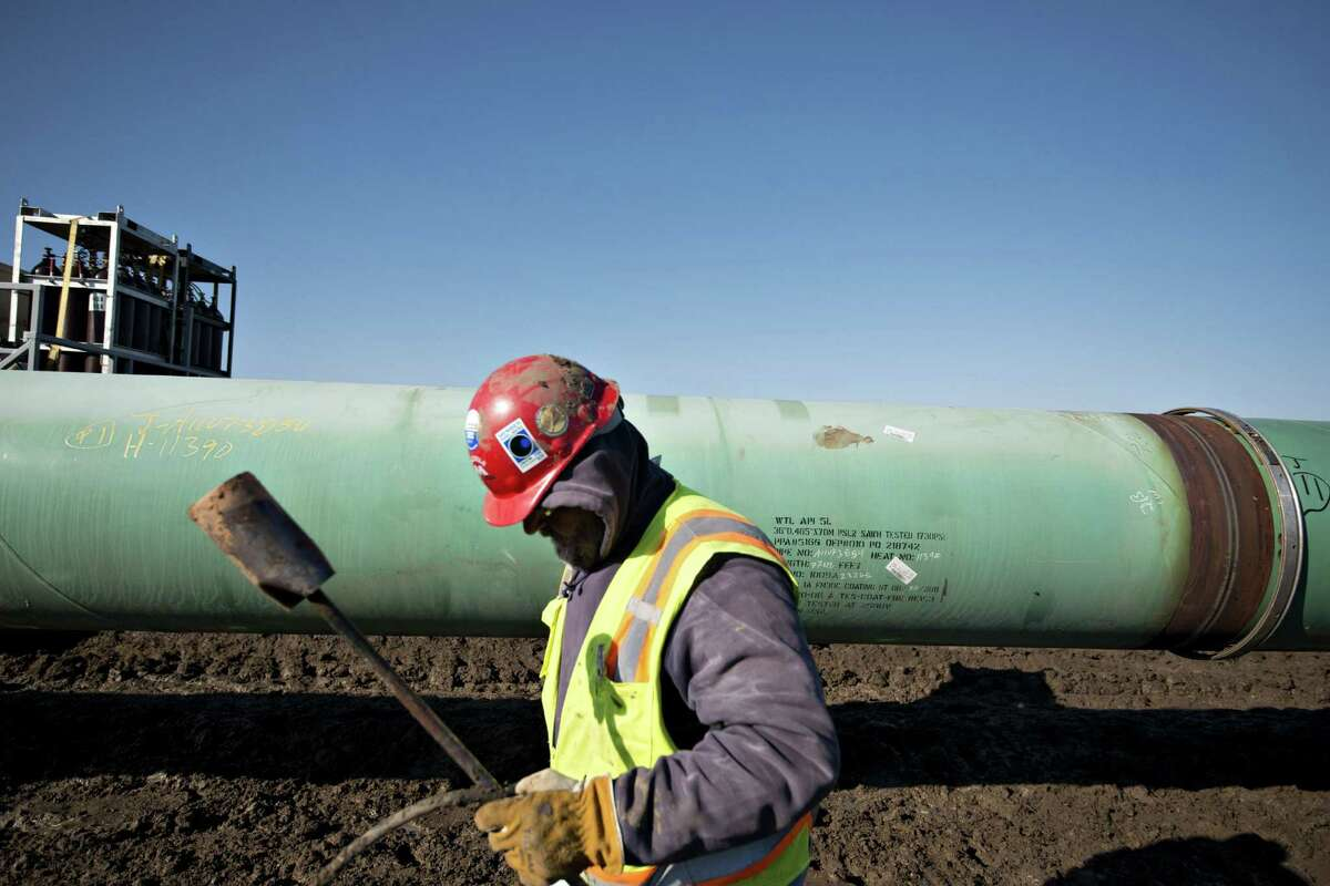 A worker carries a torch after heating a pipe joint during pipeline construction in Atoka, Okla., in March. TransCanada said it