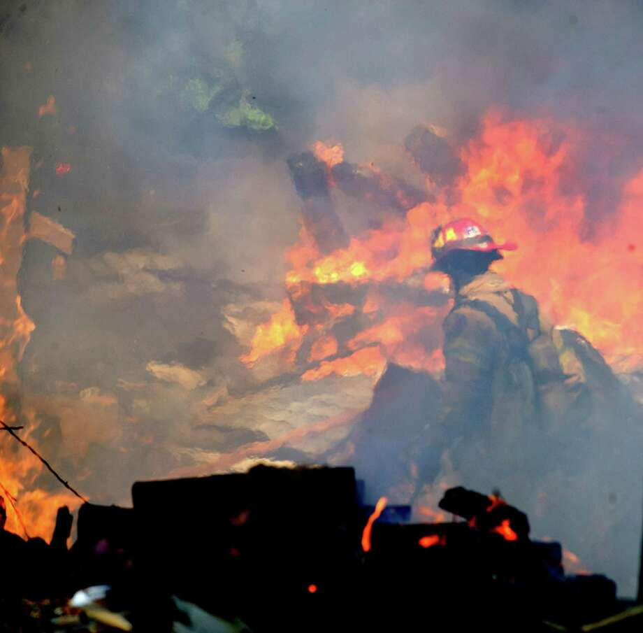 Blurred by heat and smoke, a firefighter walks through the burning rubble of 305 Webbs Hill Road in Stamford, where the home exploded on Sept. 17. Photo: Lindsay Perry / Stamford Advocate