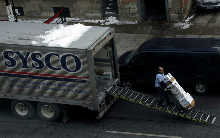 A driver for Sysco Corp. unloads supplies for a restaurant in Cleveland. Sysco is the industry leader in selling and distributing food from manufacturers to restaurants, hospitals, hotels and other institutions. Sysco is one of many Fortune 500 companies in the Lone Star State. See the rest in the following gallery. Photo: Mark Duncan, STF / AP
