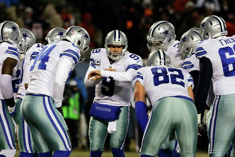Dallas Cowboys quarterback Tony Romo (9) calls a play in the huddle during the first half of an NFL