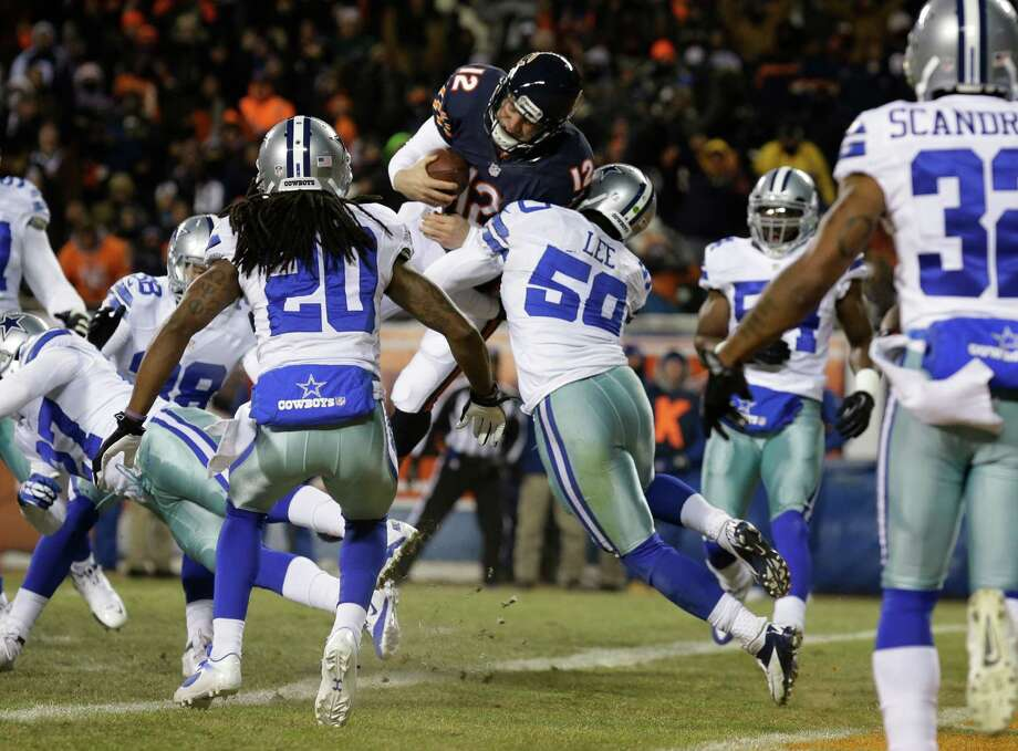 Chicago Bears quarterback Josh McCown (12) gets hit by Dallas Cowboys middle linebacker Sean Lee (50) in the air as McCown makes a touchdown run during the first half of an NFL football game, Monday, Dec. 9, 2013, in Chicago. (AP Photo/Nam Y. Huh) Photo: Nam Y. Huh, Associated Press / AP