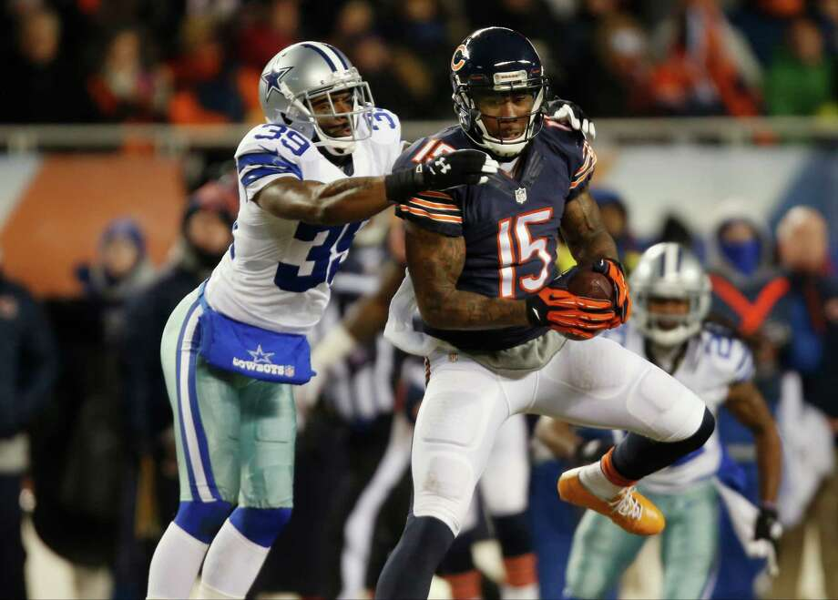 Chicago Bears wide receiver Brandon Marshall (15) makes a catch under pressure from Dallas Cowboys cornerback Brandon Carr (39) during the first half of an NFL football game, Monday, Dec. 9, 2013, in Chicago. (AP Photo/Charles Rex Arbogast) Photo: Charles Rex Arbogast, Associated Press / AP