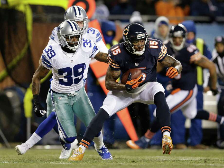 Chicago Bears wide receiver Brandon Marshall (15) runs past Dallas Cowboys cornerback Brandon Carr (39) after making a catch during the first half of an NFL football game, Monday, Dec. 9, 2013, in Chicago. (AP Photo/Nam Y. Huh) Photo: Nam Y. Huh, Associated Press / AP