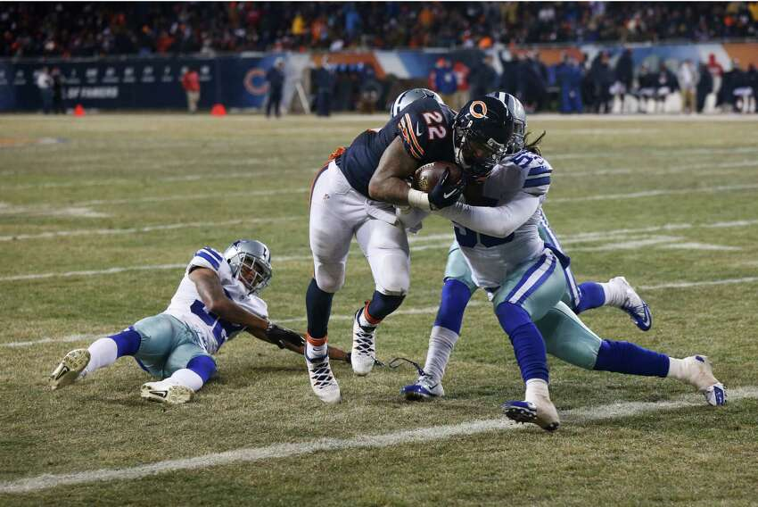 Dallas Cowboys outside linebacker Cameron Lawrence (53) tries to tackle Chicago Bears running back Matt Forte (22) as Forte makes a touchdown run during the second half of an NFL football game, Monday, Dec. 9, 2013, in Chicago. (AP Photo/Charles Rex Arbogast)