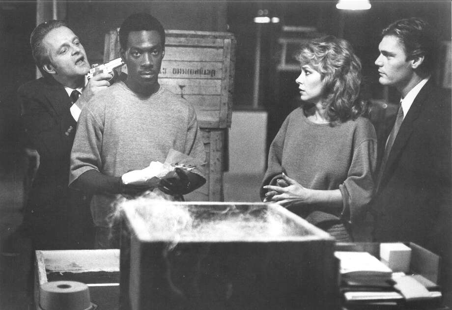 "Michael Chapman holds a gun to Eddie Murphy's head while fellow henchman Jonathan Banks holds Lisa Eilbacher after they discover a large shipment of illicit drugs in Paramount Pictures' ""Beverly Hills Cop."" Photo: Paramount Pictures"