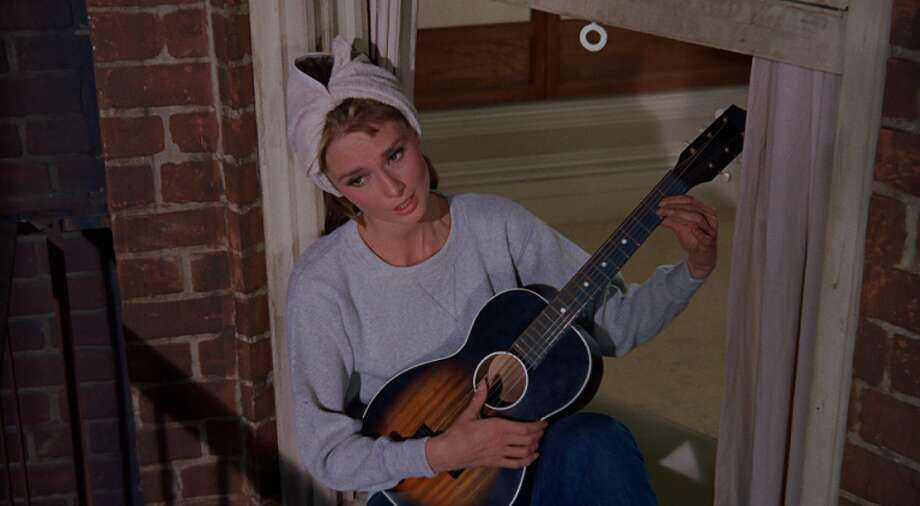 "Breakfast at Tiffany's (1961): When Holly Golightly (Audrey Hepburn) sits in her window sill and croons ""Moon River.""  Watch the clip. Photo: Paramount Pictures"
