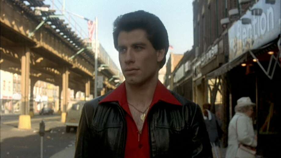 "Saturday Night Fever (1977): When Tony Manero (John Travolta) walks -- no, struts -- down the street during the opening credits to the Bee Gee's ""Stayin' Alive.""   Watch the clip. Photo: Paramount"