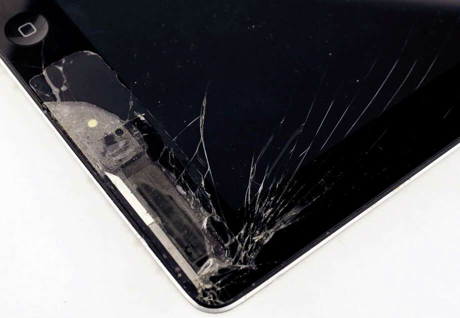 An iPad has a cracked screen in this studio photo, Friday, Dec. 6, 2013 in New York. Many plans can be started within 30 days of buying your phone, TV, camera or other gadget. In many cases, you might conclude you don't even need it. (AP Photo/Mark Lennihan) Photo: Mark Lennihan, Associated Press / Associated Press