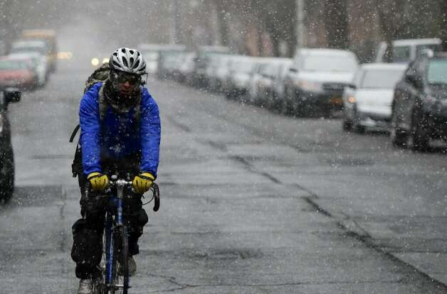 A bicyclist pedals on State Street in downtown Albany as the snow fell on Tuesday, Dec. 10, 2013. (Skip Dickstein / Times Union)