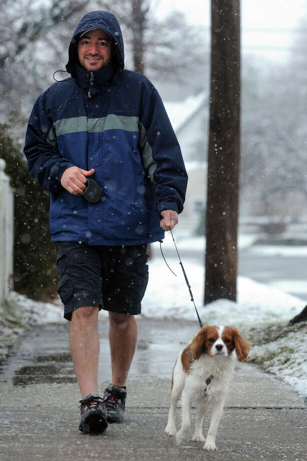 Joe Zink walks his dog, Milo, along South Ave. in Stratford, Conn. during the first snowfall of the season Dec. 10, 2013. Photo: Ned Gerard / Connecticut Post