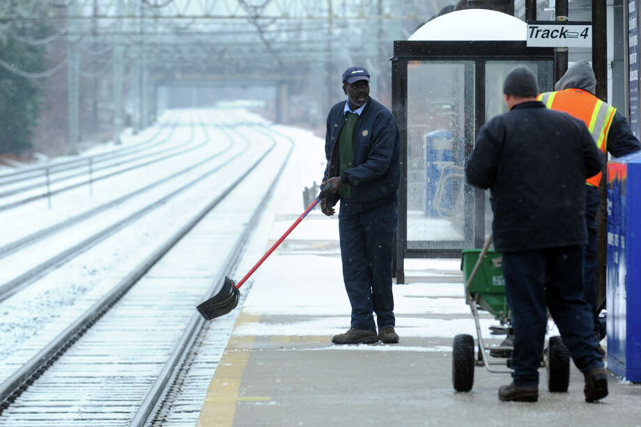Workers clear snow at the Stratford railroad station during the first snowfall of the season Dec. 10, 2013. Photo: Ned Gerard / Connecticut Post