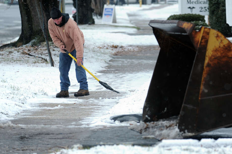 Mike Braccio shovels a sidewalk along Main St. in Stratford, Conn. during the first snowfall of the season Dec. 10, 2013. Photo: Ned Gerard / Connecticut Post