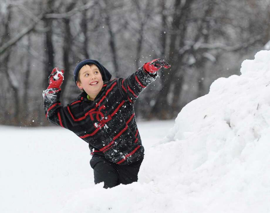 With the day off from school due to the snow, Kacper Gravowski, 10, has a snowball fight with a friend during the morning snow storm at Byram Park in Greenwich, Tuesday, Dec. 10, 2013. Photo: Bob Luckey / Greenwich Time