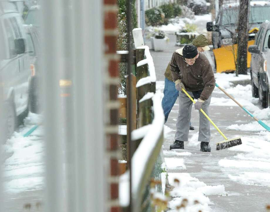 Pete Sciarrillo uses a broom to clear snow from a sidewalk during a morning snow storm on Hamilton Avenue in the Chickahominy section of Greenwich, Tuesday, Dec. 10, 2013. Photo: Bob Luckey / Greenwich Time