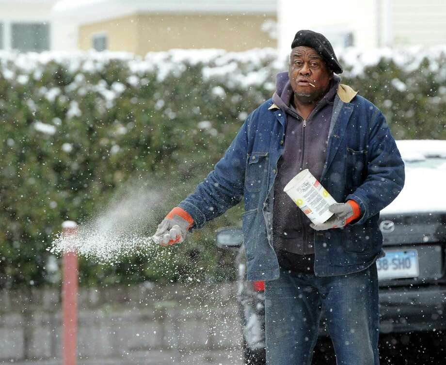 A man puts down ice-melt during a morning snow storm in a driveway on Hamilton Avenue in Greenwich, Tuesday, Dec. 10, 2013. Photo: Bob Luckey / Greenwich Time