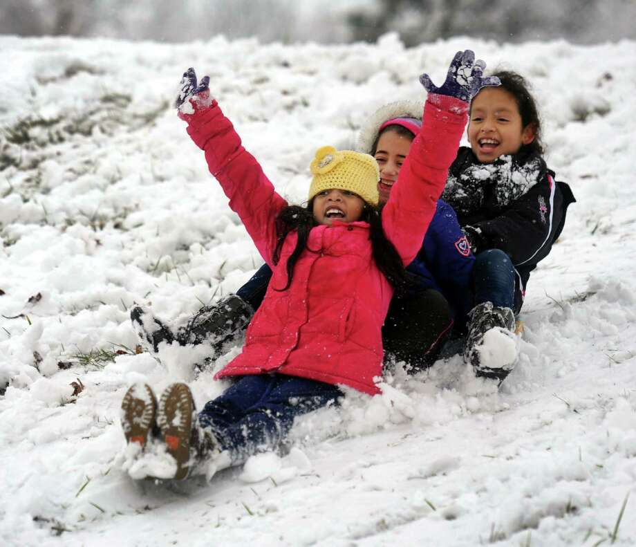 From left, Alyssa Fabia, 8, Natalie De La Cruz, 5, and Rolselyn Blanco, 9, sled down a hill in a backyard on Mill Ridge Road in Danbury, Conn. Tuesday, Dec. 10, 2013. Photo: Carol Kaliff / The News-Times