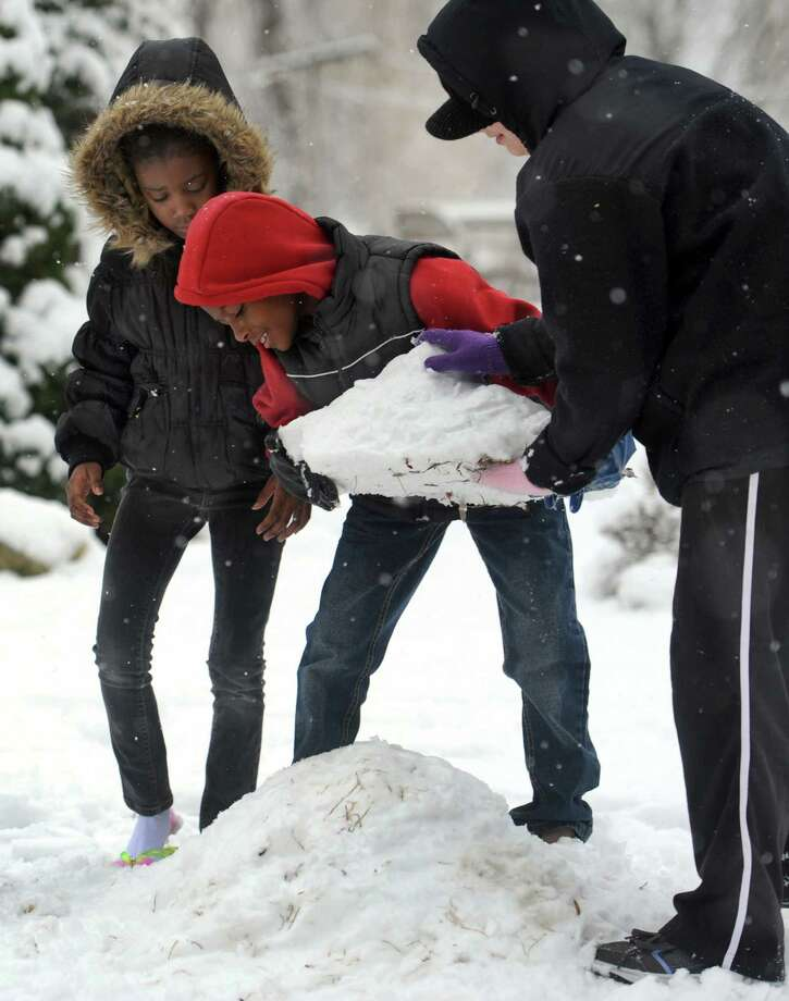 From left, Jamauree Reynoso, 8, Devin Reynoso, 10, and Samantha Marie Lake-Lane, 11, build the foundation for a snowman on High Ridge Road in Danbury, Conn., Tuesday, Dec. 10, 2013. Photo: Carol Kaliff / The News-Times