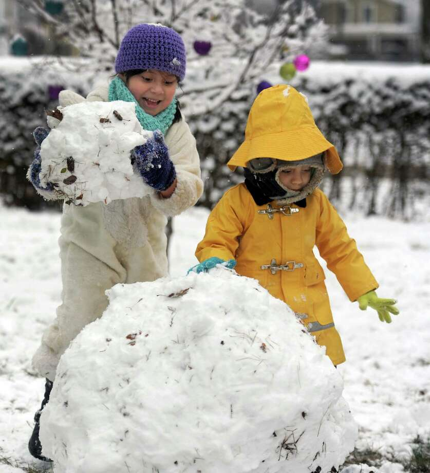 Daisy Jara, 6, left, and her brother Branny, 4, build a snowman in their yard on 9th Avenue in Danbury, Conn., Tuesday, Dec. 10, 2013. School kids in Greater Danbury had a snow day on Tuesday. Photo: Carol Kaliff / The News-Times