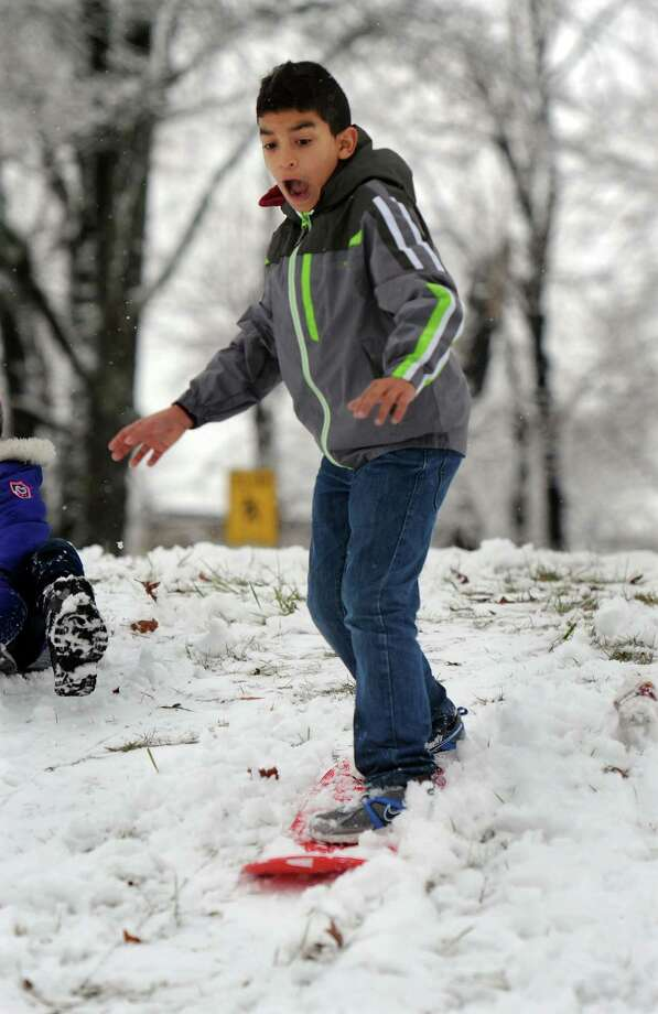 Javier Estevec, 10, snowboards down a hill on Mill Ridge Road in Danbury, Conn. Tuesday, Dec. 10, 2013. Photo: Carol Kaliff / The News-Times