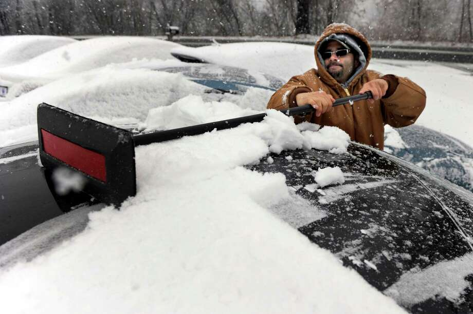 Jose Roman cleans snow off the cars at Colonial Mazda on Federal Road in Danbury, Conn. Tuesday, Dec. 10, 2013. Photo: Carol Kaliff / The News-Times