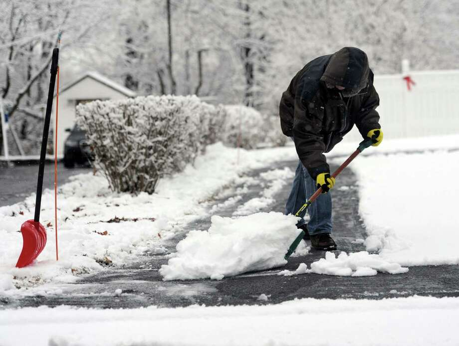 Meguel Perez shovels the snow in his driveway on Abbott Avenue in Danbury, Conn. Tuesday, Dec. 10, 2013. Photo: Carol Kaliff / The News-Times
