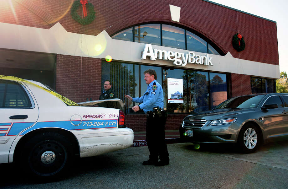 A police officer walks into an AmegyBank in the 1300 block of Wirt Road, Tuesday, Dec. 10, 2013, in Houston. Officials said at least one suspect with a gun robbed the bank around 10:30 a.m. Authorities surrounded the suspect near the property of Aldine High School near Airline and West Road where they later took him into custody. Photo: Cody Duty, Houston Chronicle / © 2013 Houston Chronicle
