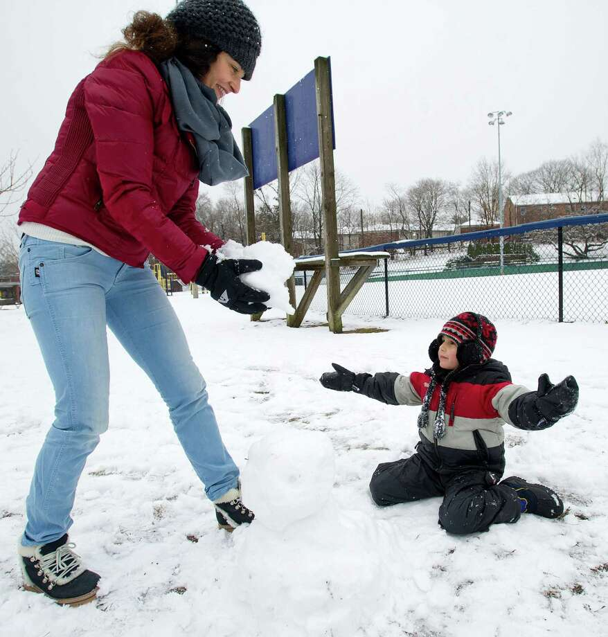 Andrei Orasanu, 5, and his aunt, Adela Keogh, make a snowman at Springdale Elementary School in Stamford, Conn., on Tuesday, December 10, 2013. Photo: Lindsay Perry / Stamford Advocate