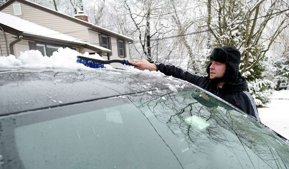 Kevin Baranowski brushes snow off a car on Boutin St. West in Stamford, Conn., on Tuesday, December 10, 2013. Photo: Lindsay Perry / Stamford Advocate