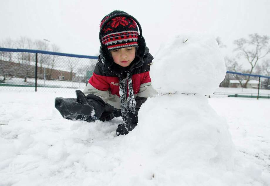 Andrei Orasanu, 5, makes a snowman at Springdale Elementary School in Stamford, Conn., on Tuesday, December 10, 2013. Photo: Lindsay Perry / Stamford Advocate