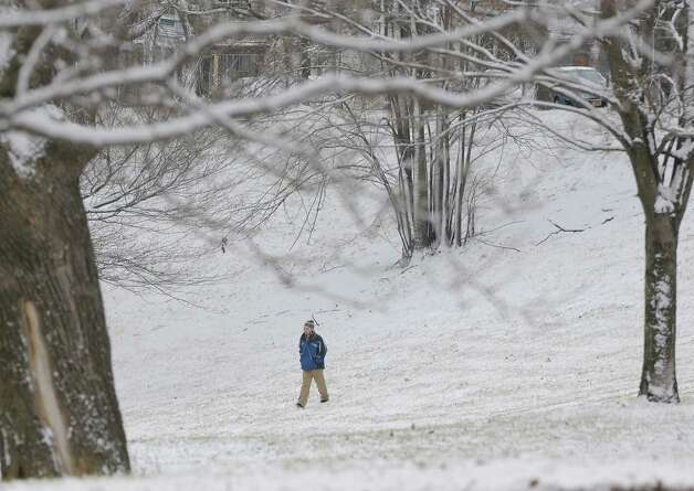 Sean Phillips of Albany walks through a snow covered Lincoln Park Tuesday, Dec. 10, 2013, in Albany, N.Y. (Lori Van Buren / Times Union) Photo: Lori Van Buren / 00024968A