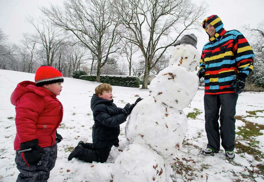 From left, Raffy Rabins, 3, his brother Benjamin Rabins, 5, and their au pair, Fabian Prebio, make a snowman in Bruce Park in Greenwich, Conn., on Tuesday, December 10, 2013. Photo: Lindsay Perry / Stamford Advocate