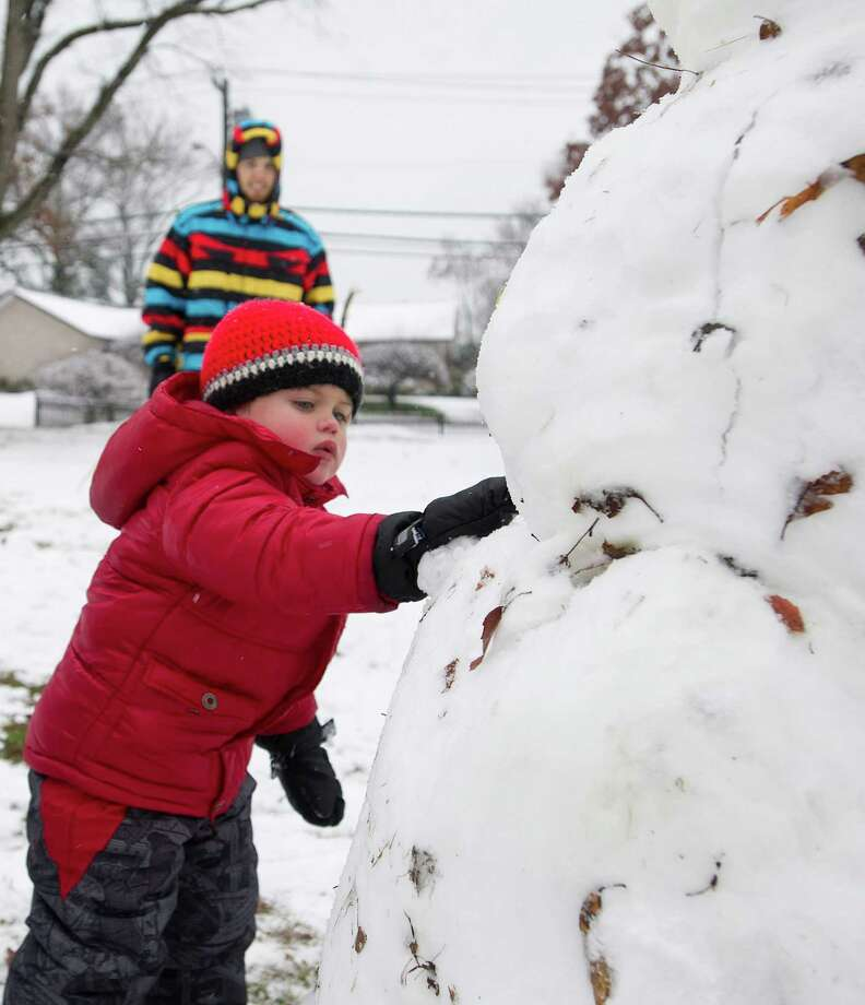 Raffy Rabins, 3, helps make a snowman in Bruce Park in Greenwich, Conn., on Tuesday, December 10, 2013. Photo: Lindsay Perry / Stamford Advocate