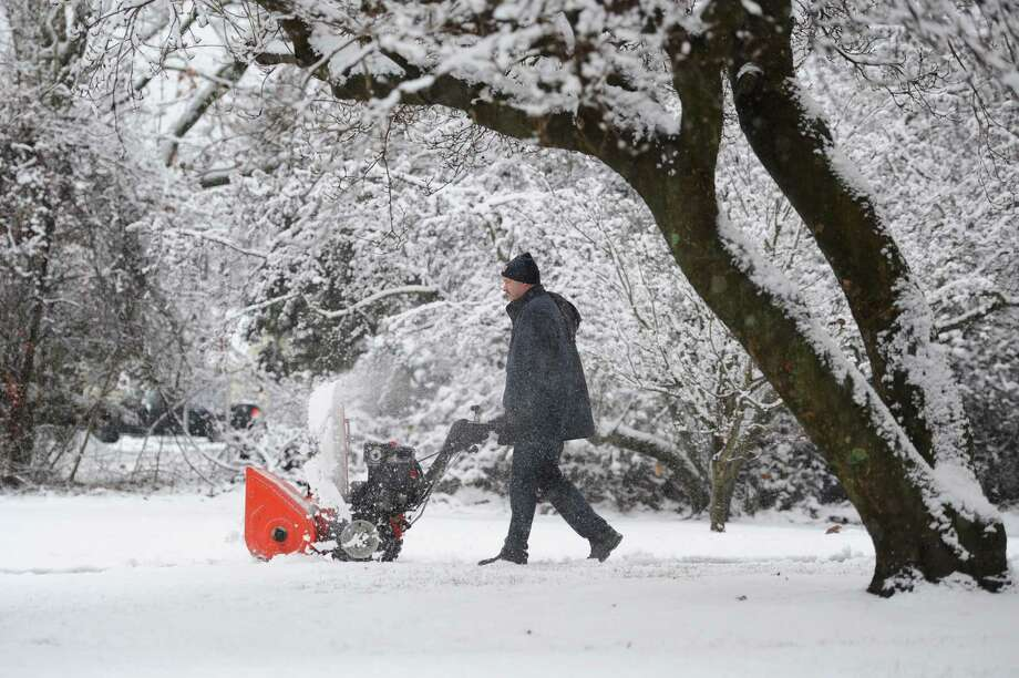 Steve Carlson, an employee of Newtown Public Schools, clears off the snow in front of Hawley School with a snowblower in Newtown, Conn. on Tuesday, Dec. 10, 2013.  Wednesday's forecast is expected to be in the low 30s and mostly sunny. Photo: Tyler Sizemore / The News-Times
