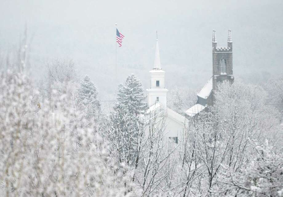 Snow falls over Newtown at the flagpole, Newtown Congregational Church, center, and Trinity Episcopal Church on Tuesday, Dec. 10, 2013.  Wednesday's forecast is expected to be in the low 30s and mostly sunny. Photo: Tyler Sizemore / The News-Times