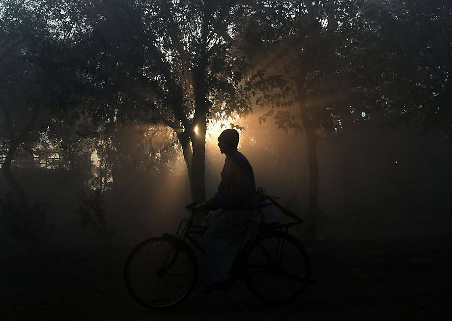 Pedaling milk: A Pakistani milkman delivers milk by bicycle on a foggy day in Lahore. Photo: Arif Ali, AFP/Getty Images