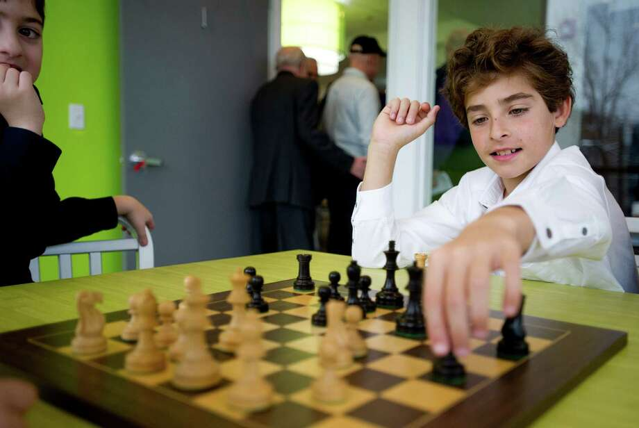 Frederico Gazal, 11, plays chess during a grand opening ceremony for Zaniac, a kid's learning center, in Greenwich, Conn., on Tuesday, December 10, 2013. Photo: Lindsay Perry / Stamford Advocate
