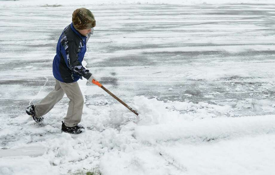 Leo Castagna, Jr., 7, of Newtown, shovels snow in the parking lot of Botsford Drive-In in Newtown, Conn. on Tuesday, Dec. 10, 2013.  Wednesday's forecast is expected to be in the low 30s and mostly sunny. Photo: Tyler Sizemore / The News-Times