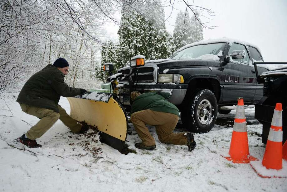 Kristopher Castagna, left, and his brother Leo Castagna, of Newtown, fix a plow on the front of their truck to plow a parking lot in Newtown, Conn. on Tuesday, Dec. 10, 2013.  Wednesday's forecast is expected to be in the low 30s and mostly sunny. Photo: Tyler Sizemore / The News-Times