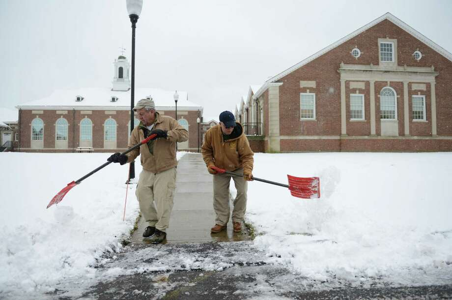 Mike Csanadi, left, and Amandio Dos Santos, employees of Newtown Parks and Recreation, shovel snow on the Fairfield Hills campus in Newtown, Conn. on Tuesday, Dec. 10, 2013.  Wednesday's forecast is expected to be in the low 30s and mostly sunny. Photo: Tyler Sizemore / The News-Times