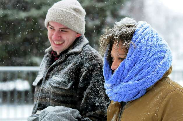 Dan Durham, left, and his girlfriend Jammella Anderson, both of Albany, get caught in the snow on Tuesday, Dec. 10, 2013, at the Empire State Plaza in Albany, N.Y. They had hoped to ice skate, but the rink was closed while workers improve the ice conditions. It reopens on Friday at 11 a.m. for Hannaford's Free Skate Rental Friday. (Cindy Schultz / Times Union) Photo: Cindy Schultz / 00024968A