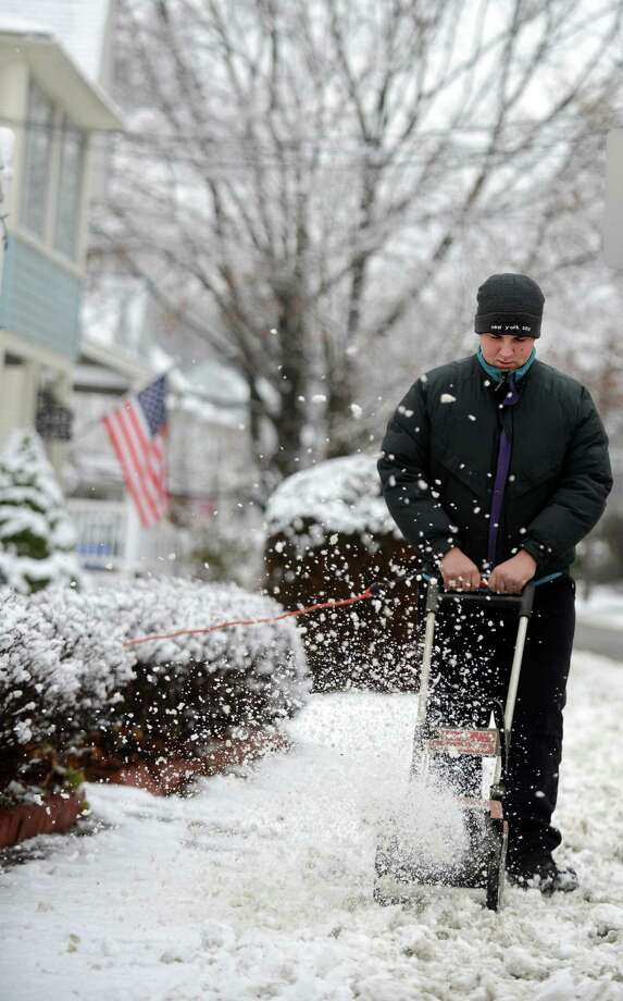 Fifteen-year-old Tim Schmidheini uses clears snow from the sidewalk in front of his house in Ansonia, Conn. Tuesday, Dec. 10. 2013. Photo: Autumn Driscoll / Connecticut Post
