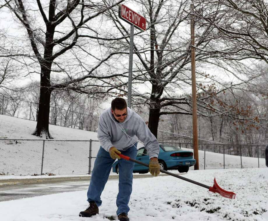 Tom McEvoy, of Derby, clears snow from the sidewalk near McEvoy Place in Derby, Conn., named after his uncle, Marine Sgt. Eugene McEvoy who fought in World War II, Tuesday, Dec. 10, 2013. Photo: Autumn Driscoll / Connecticut Post
