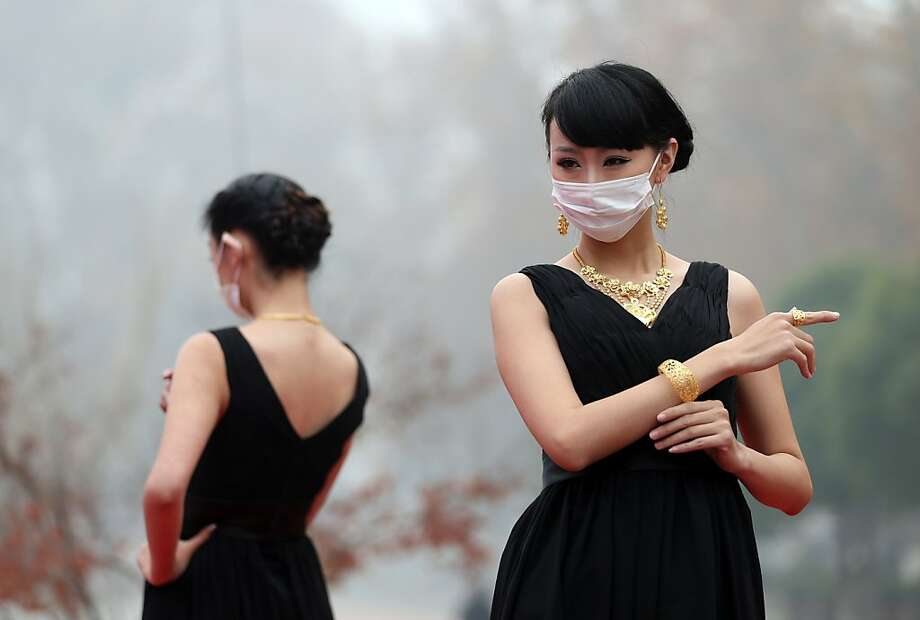 If you can't show your face, show your bling:With air pollution reaching as much as 40 times World Health Organization limits, models don surgical masks before presenting gold jewelry at an outdoor fashion show in Nanjing. Photo: Stringer, AFP/Getty Images