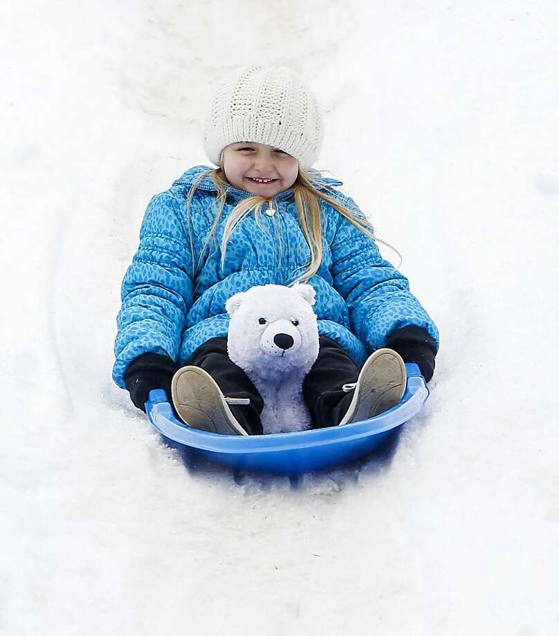 Bear on board: Five-year-old Skylar Rose Roberson rides the polar express to the bottom of a snow-covered slope at Winterfest Helotes in Helotes, Texas. Photo: Marvin Pfeiffer, Prime Time Newspapers
