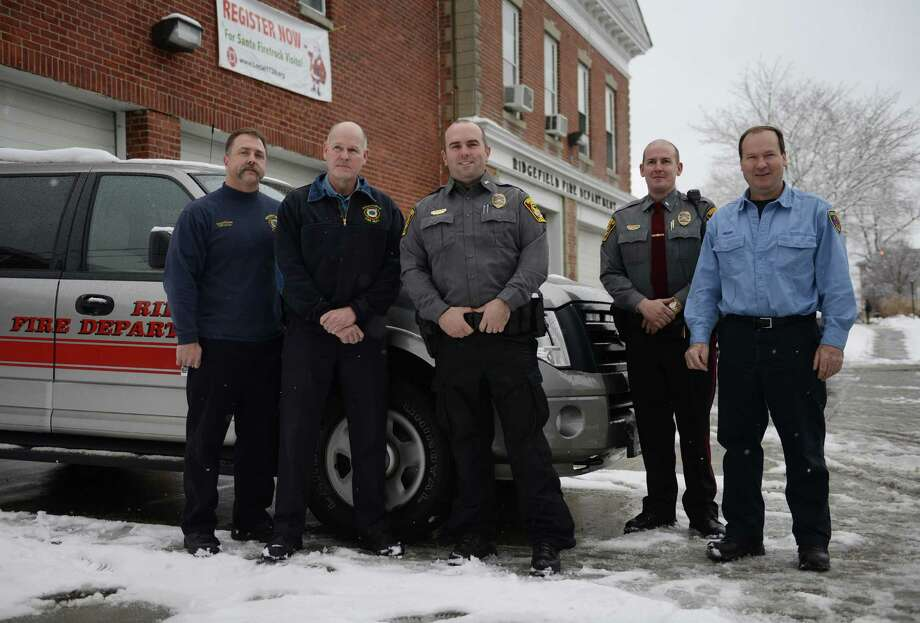 Members of the Ridgefield Fire and Police Department stand in front of the firehouse on Catoonah Street in Ridgefield, Conn. on Tuesday, Dec. 10, 2013.  The officers and firefighters helped a woman deliver a baby on Tuesday morning.  The slick roads kept the couple from driving to the hospital, so the dispatcher assisted the couple on the phone as two officers and two firefighters went to the family's home.  From left, dispatcher Dennis Frulla, fire Capt. John Drake, police officer Chris Daly, police Lt. Jeff Smith, and firefighter Mike Drake. Photo: Tyler Sizemore / The News-Times