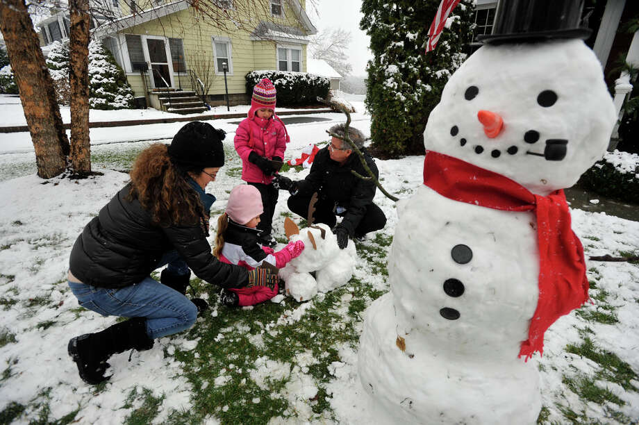 The Berry family, from left, Jennifer, Sophie, Maya(standing) and Geoffrey, works on a snow reindeer after making a snowman in front of their house in Stamford, Conn., after the first snow accumulation on Tuesday, Dec. 10, 2013. According to the National Weather Service at 11 a.m. the snow total for Stamford reached 1.5 inches. Photo: Jason Rearick / Stamford Advocate