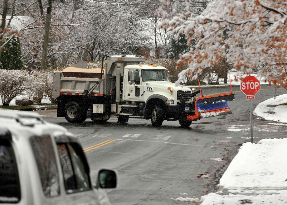 A city plow and salt spreader makes its way around the city after the first snow accumulation in Stamford, Conn., on Tuesday, Dec. 10, 2013. According to the National Weather Service at 11 a.m. the snow total for Stamford reached 1.5 inches. Photo: Jason Rearick / Stamford Advocate