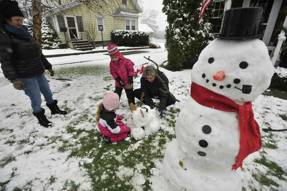 The Berry family works on a snow reindeer after making a snowman in front of their house in Stamford, Conn., after the first snow accumulation on Tuesday, Dec. 10, 2013. According to the National Weather Service at 11 a.m. the snow total for Stamford reached 1.5 inches. Photo: Jason Rearick / Stamford Advocate