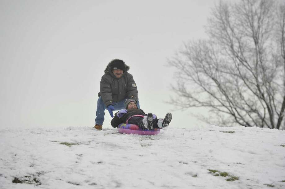 Edwin Diaz pushes her daughter, Krystal, down a hill at E. Gaynor Brennan Municipal Golf Course after the first snow accumulation in Stamford, Conn., on Tuesday, Dec. 10, 2013. According to the National Weather Service at 11 a.m. the snow total for Stamford reached 1.5 inches. Photo: Jason Rearick / Stamford Advocate